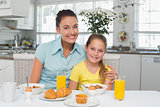 Mother and daughter sitting at breakfast table