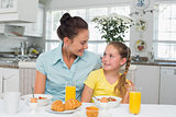 Girl looking at mother while having breakfast