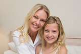 Mother and girl smiling in bedroom