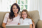 Mother and daughter with laptop on sofa
