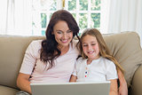 Mother and daughter using laptop together on sofa