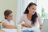 Woman using technologies while daughter studying at table