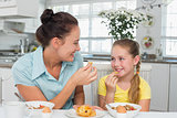 Mother and daughter having muffin at breakfast table