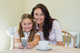 Woman and daughter holding mobile phone at table