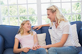 Mother and daughter sitting on sofa at home
