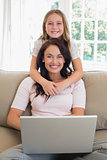 Girl with mother using laptop on sofa
