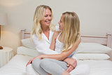 Mother and daughter looking at each other in bed