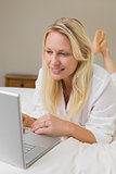 Blond woman using laptop in bed