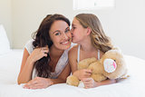 Cute girl kissing mother on cheek in bed