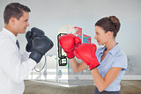 Composite image of colleagues in competition having a boxing match