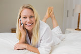 Woman using mobile phone while lying in bed