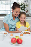 Mother and daughter reading greeting card at breakfast table
