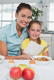 Woman with daughter reading greeting card at breakfast table