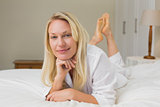 Confident woman lying in bed