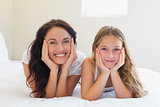 Mother and daughter with head in hands on bed