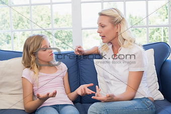 Angry mother scolding daughter on sofa