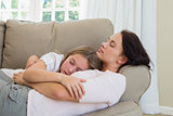 Mother and daughter sleeping on sofa