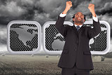 Composite image of happy businessman with raised arms