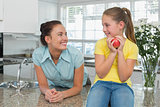 Woman looking at daughter holding apple in kitchen