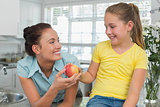 Girl giving apple to mother in kitchen