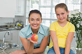 Woman showing apple by daughter in kitchen