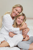 Happy mother hugging cute daughter in bed