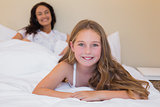 Girl lying in bed with mother in background