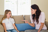 Mother scolding girl while sitting on sofa
