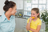 Mother looking at daughter eating orange in kitchen