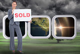 Composite image of happy real estate agent with sold sign