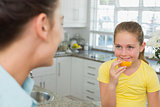 Girl having orange while looking at mother