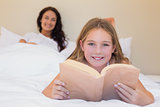 Girl holding book in bed with mother in background