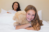 Girl embracing teddy bear with mother in background