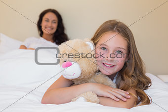 Little girl embracing teddy bear with mother in background