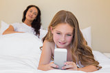 Girl using mobilephone on bed with mother in background