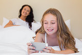 Girl using cellphone on bed with mother in background
