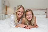 Woman with daughter lying in bed at home