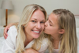Girl kissing mother on cheek in bed