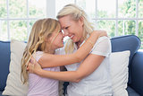 Mother and daughter rubbing noses on sofa
