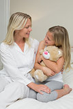 Girl embracing teddy bear while looking at mother in bed