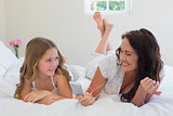 Mother and daughter enjoying music on MP3 player in bed