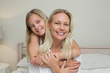 Girl embracing mother from behind in bed