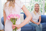 Mother looking at girl hiding flower bouquet behind back