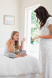 Mother and daughter arguing in bedroom