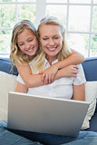 Girl embracing mother using laptop