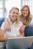 Happy mother and daughter with laptop in house