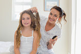 Mother making hair of daughter in bedroom