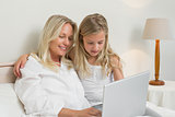 Girl and mother using laptop in bedroom