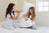 Mother and daughter having pillow fight in bed