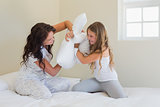 Mother and daughter pillow fighting in bed